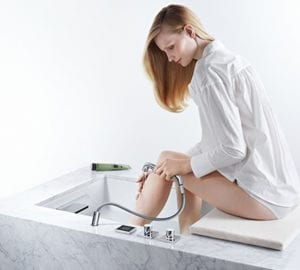 a woman using a shower attachment to wash her legs