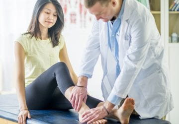 A woman is working with a physical therapist on her ankle injury.