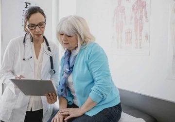 female doctor treating older female patient