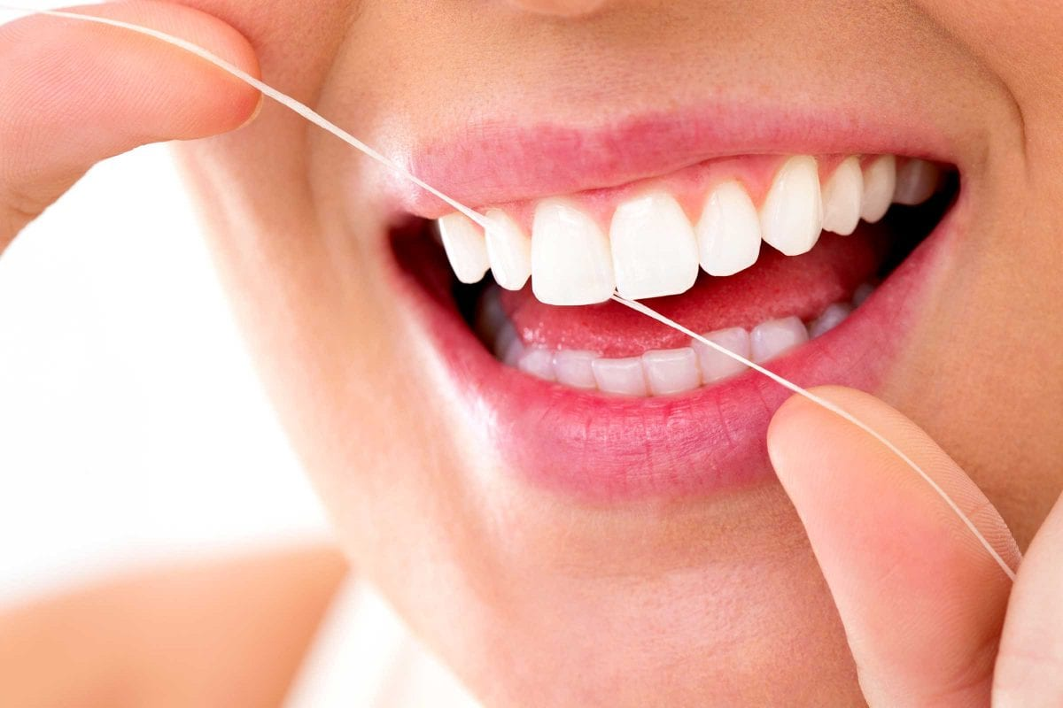 Woman smiling with flossing her teeth