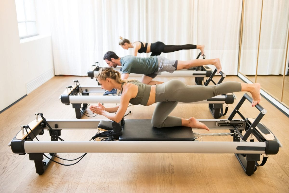 people using a reformer in their pilates class