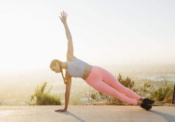 woman doing a side plank outdoors
