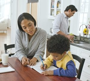 a family sitting in the kitchen doing homework