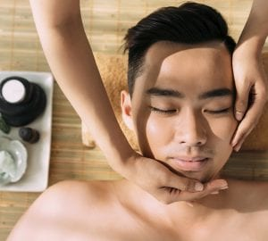 Young man receiving facial massage at the spa center, view from the top