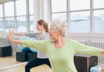 women doing yoga in a well lit studio