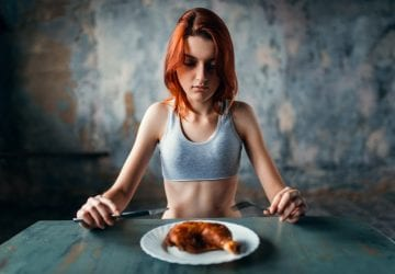 thin teen sitting in front of a plate of food