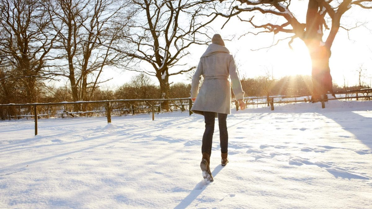 Young woman walking in the snow into the sunset