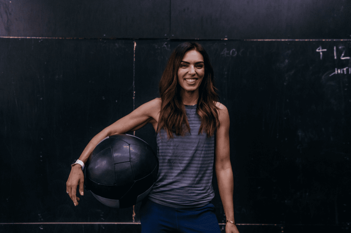 a fit woman standing in the gym with a medicine ball