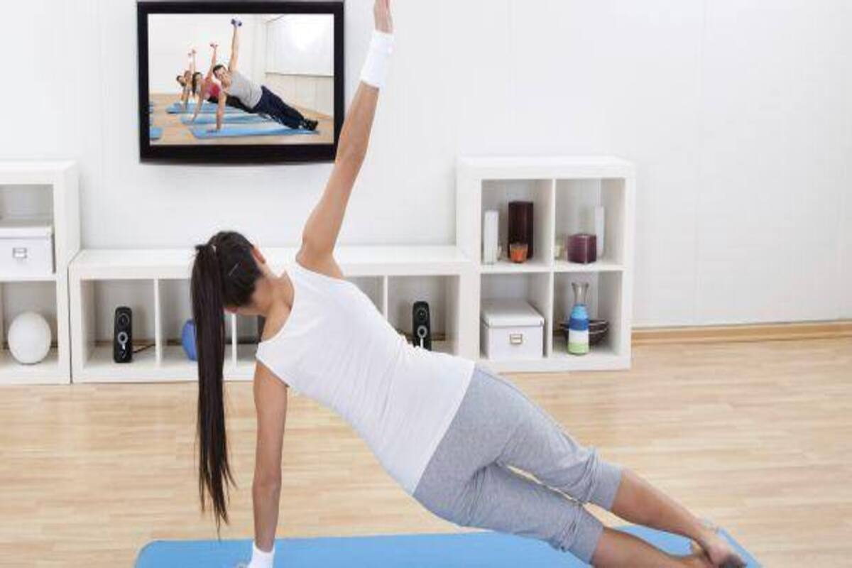 waman exercising in front of a TV