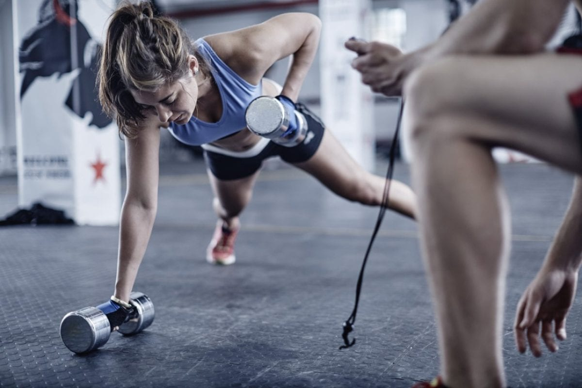 woman doing dumbell wows while working out