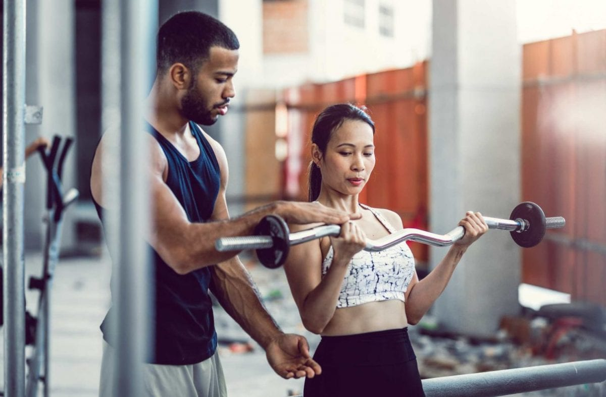 woman getting help by a personal trainer