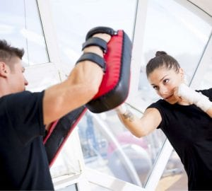 Woman hitting boxing pads with her trainer