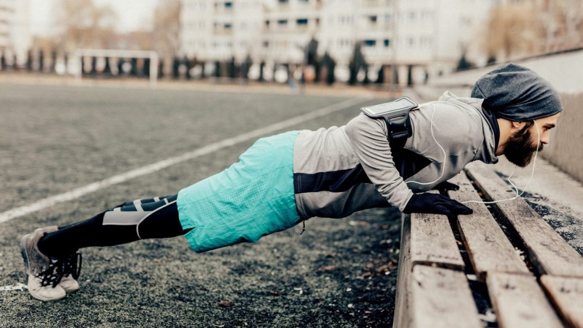 athlete doing push-ups on an outdoor bench