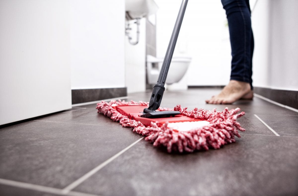 woman cleaning the floor with a mop