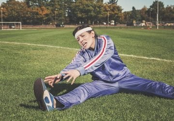 woman stretching in agony on a soccer field