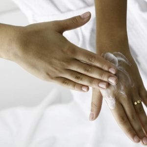 dry hands being moisturized