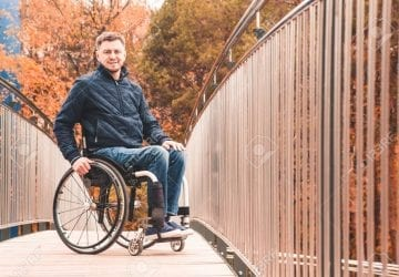 Man in a wheelchair use a wheelchair ramp