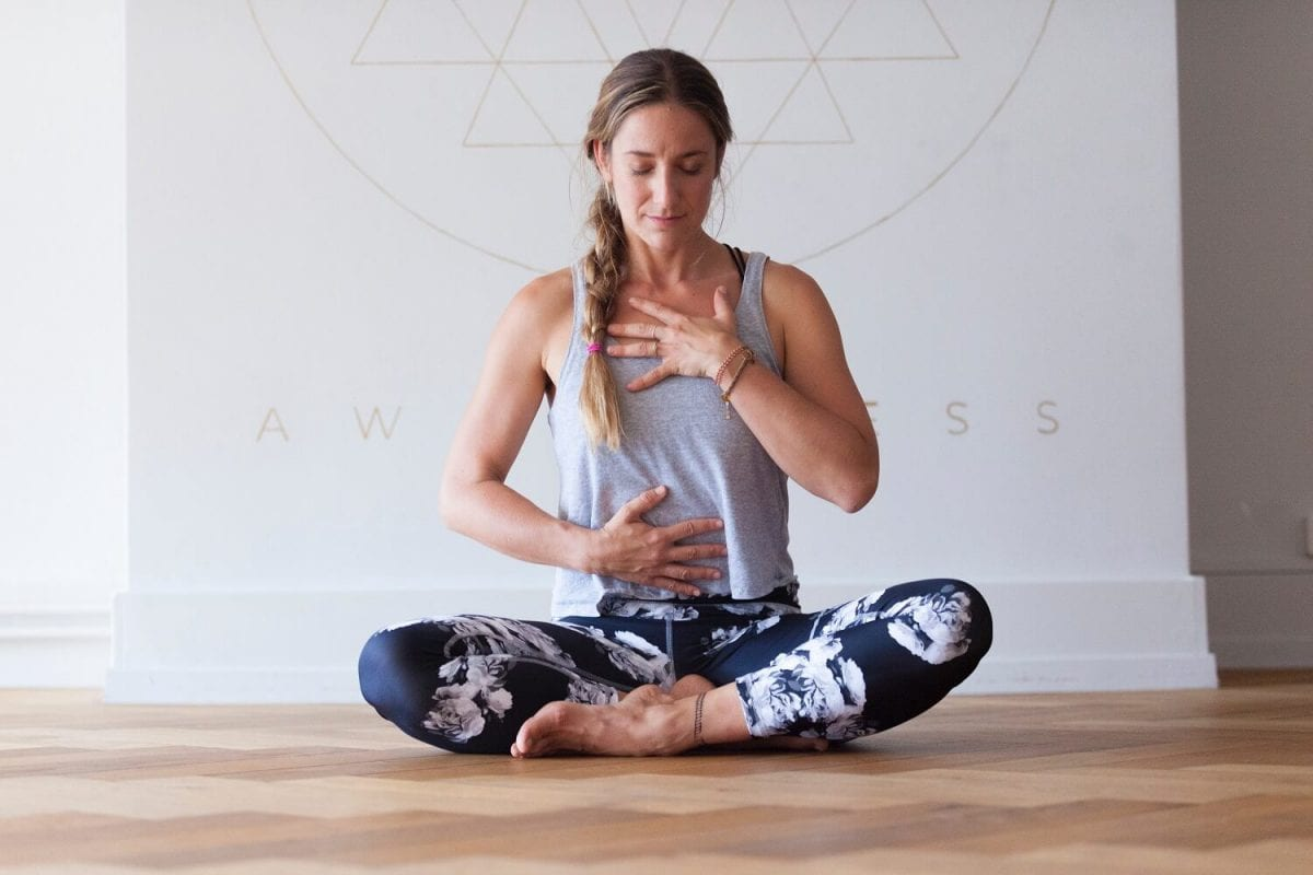 woman sitting down doing breathing exercises