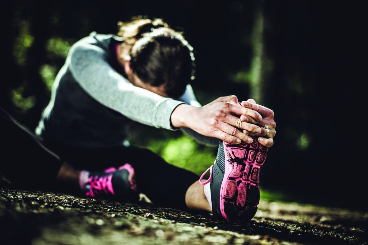 A dark moody image of a woman in her early 30's stretching her legs in a bright Pacific Northwest forest after a jog. Selective focus on her shoe and hands in the foreground, her shoes dirty from a gruelling run.