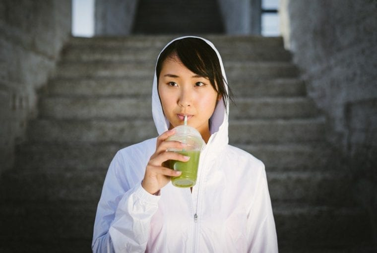 woman drinking a green snmoothie