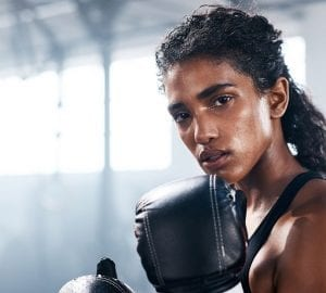 woman boxing in a gym looking into the camera