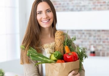 woman standing in her kitchen with a bag of groceries