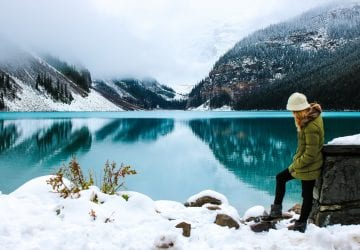 a woman standing in front of a lake in the winter