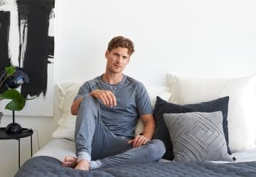 man sitting in his pyjamas in bed