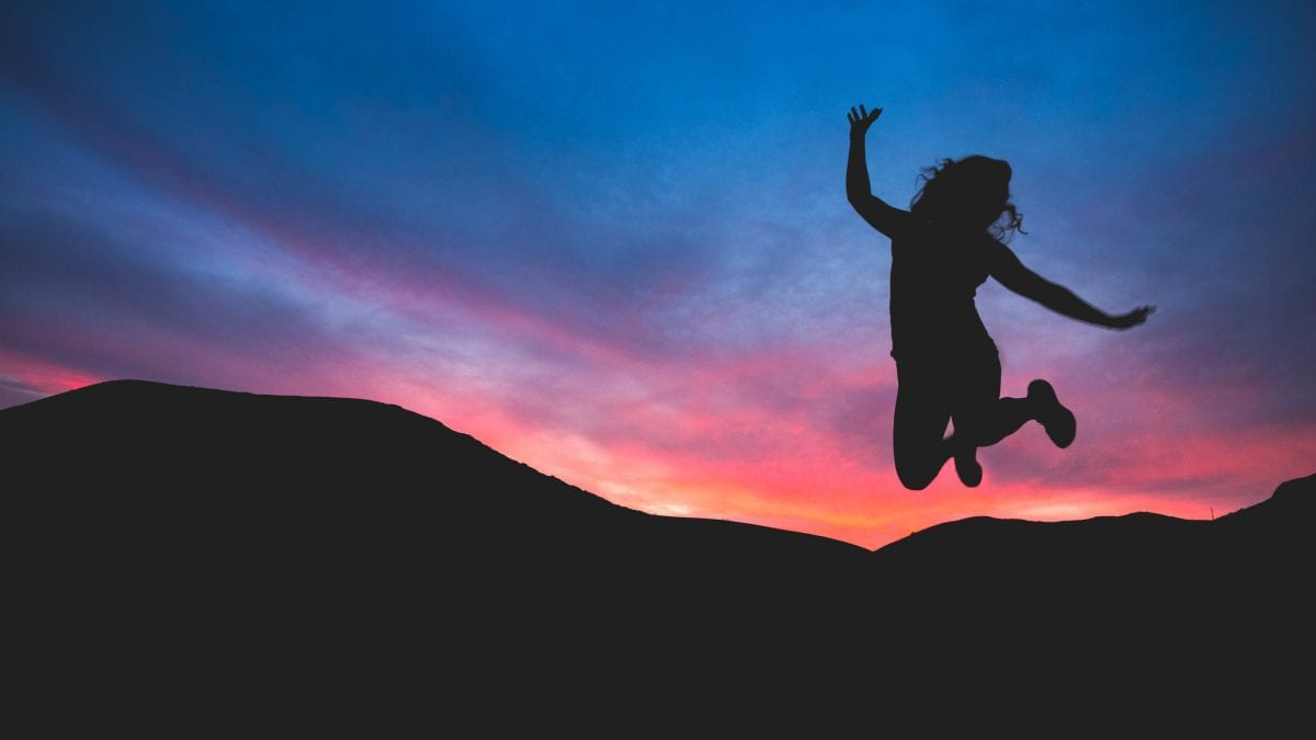 A woman jumping outdoors at sunrise