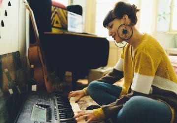 a woman playin gkeyboard in her living room