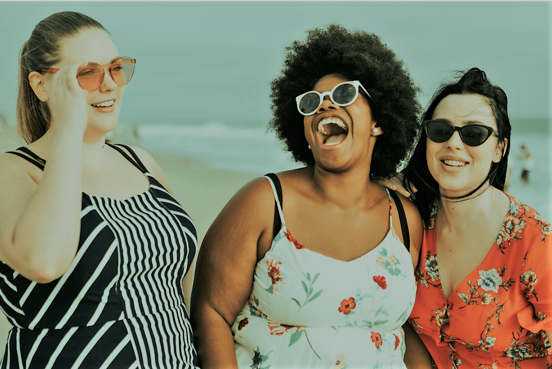 a group of women laughing on the beach