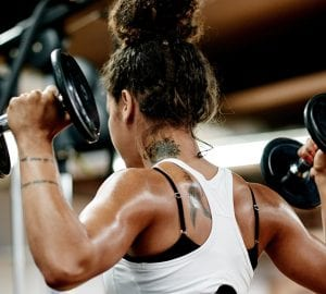 a woman doing a shoulder workout at the gym