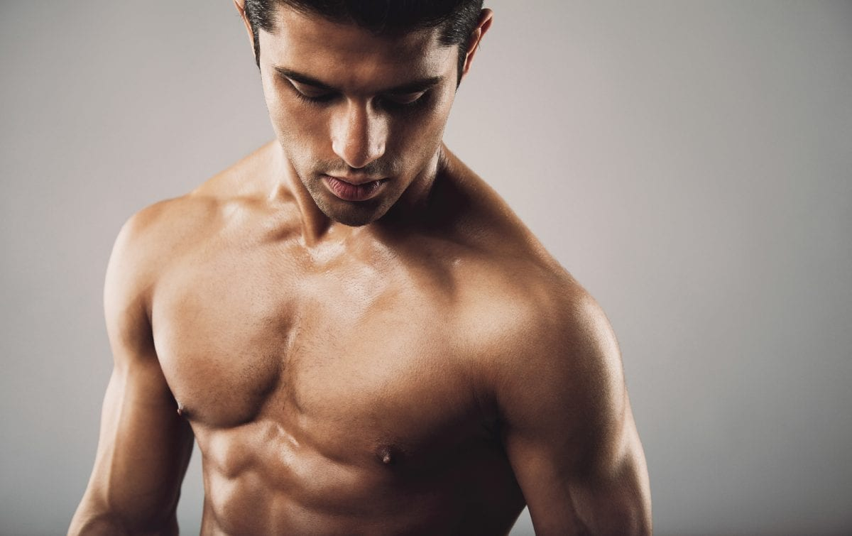 Portrait of fit muscular shirtless man looking down. Hispanic male model on grey background. Workout and fitness theme.