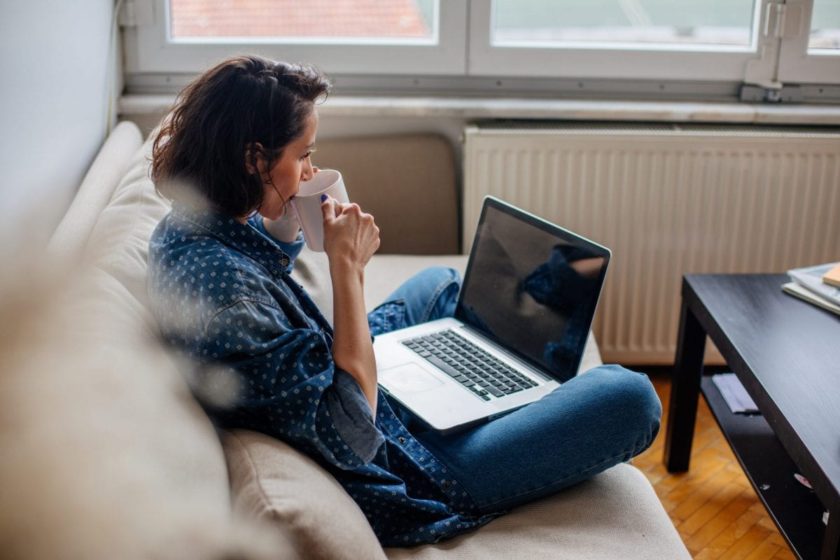 woman drinking coffee while on her computer