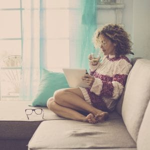 beautiful middle age woman with curly hair working at home and relaxing on the sofa with a tablet and internet. drinking tea or lemonade. happy relaxed leisure activity indoor