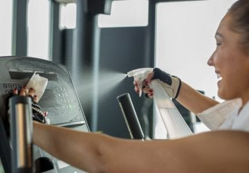 Woman cleaning work out area at the gym