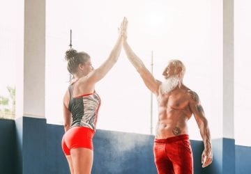 Fitness couple stacking hands in gym wellness club - Happy athletes motivating each other - Concept of people training, fit, empowering and bodybuilding lifestyle