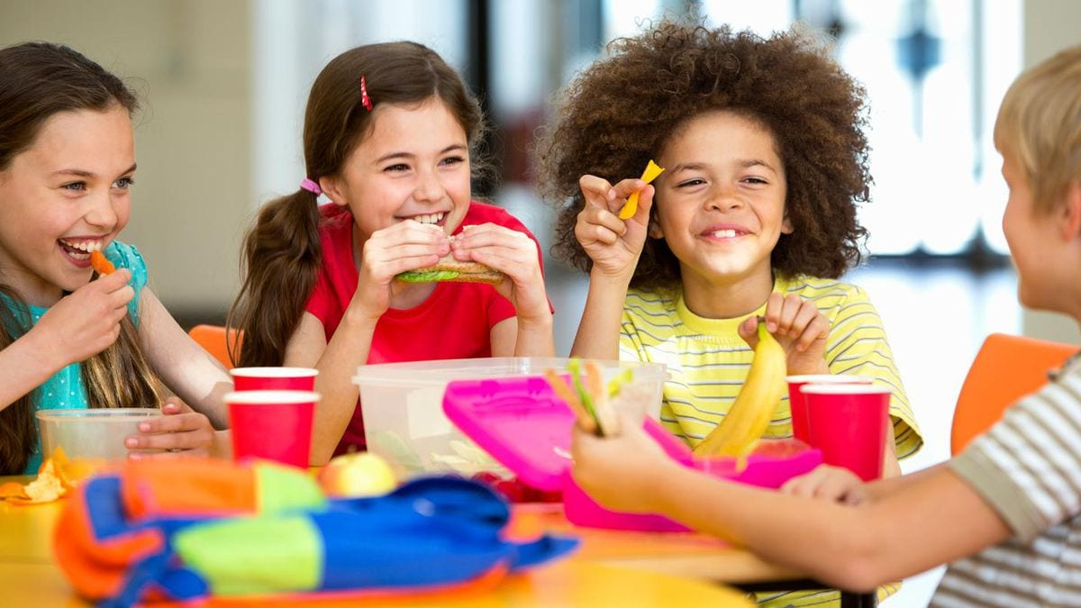 a group of kids eating a healthy meal