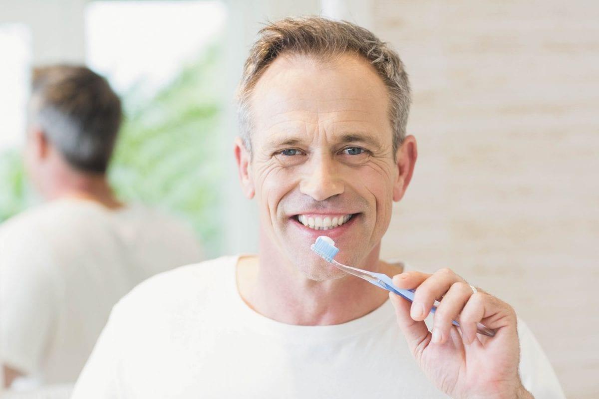 A man brushing his teeth in the bathroom