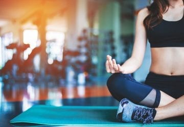 a woman meditating in the gym