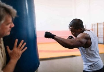 a man boxing with a heavy bag
