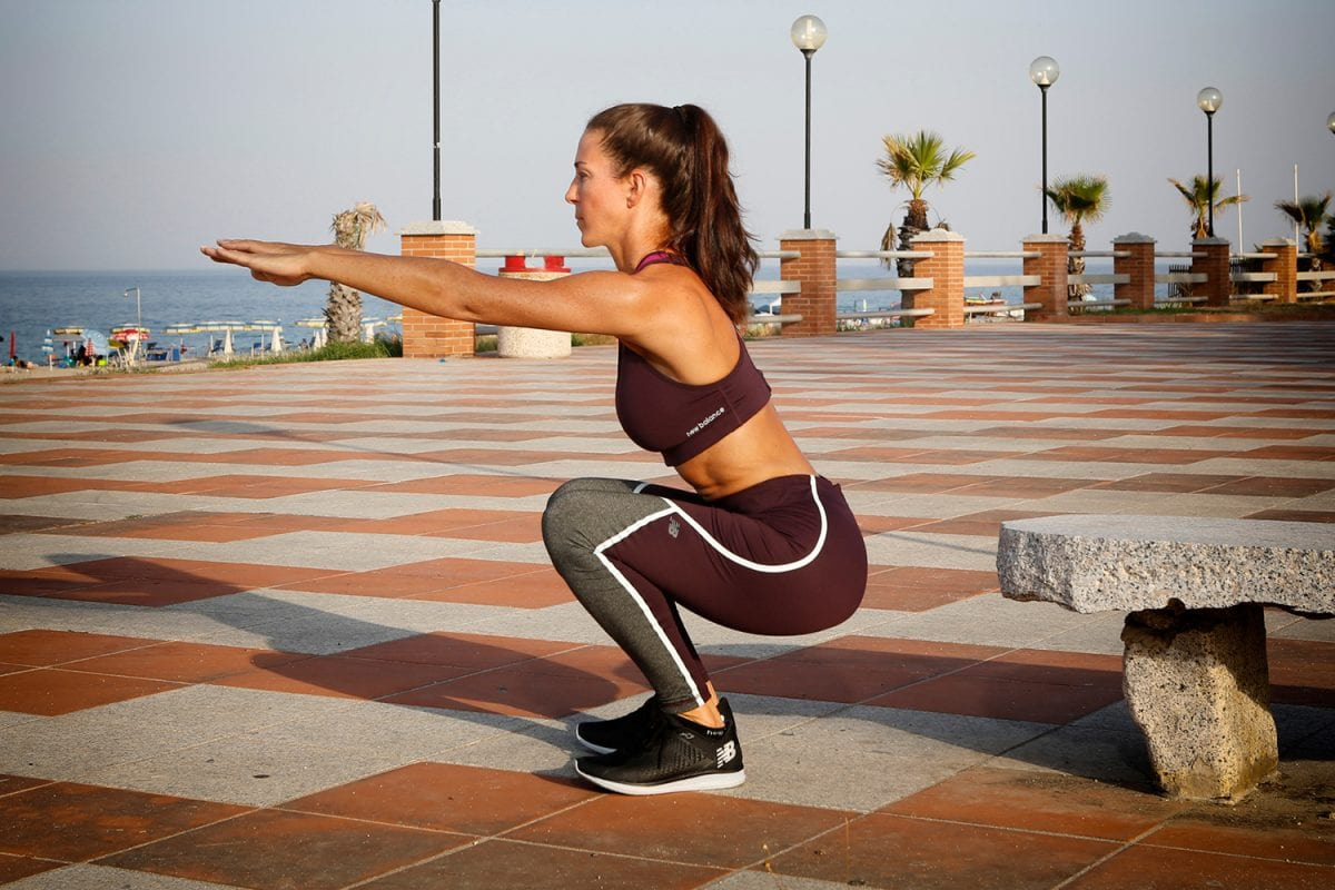 a woman doing body weight squats outdoors