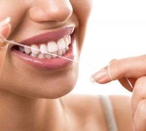 a woman using dental floss