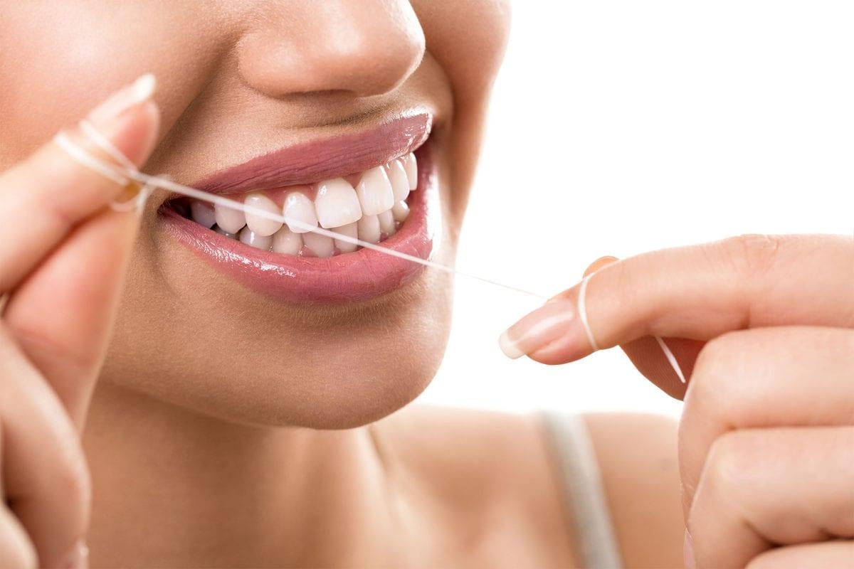 a woman using dental floss