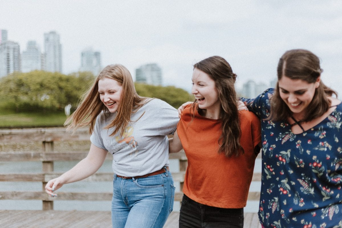 a group of friends walking and laughing outdoors