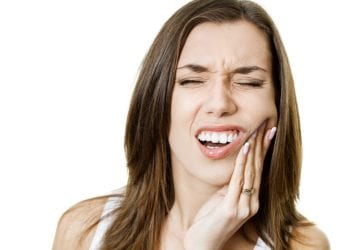 Young woman suffering from toothache and holding a hand on a jaw.
