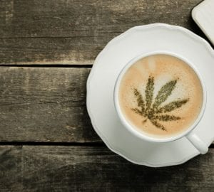 a cup of coffee with a cannabis leaf