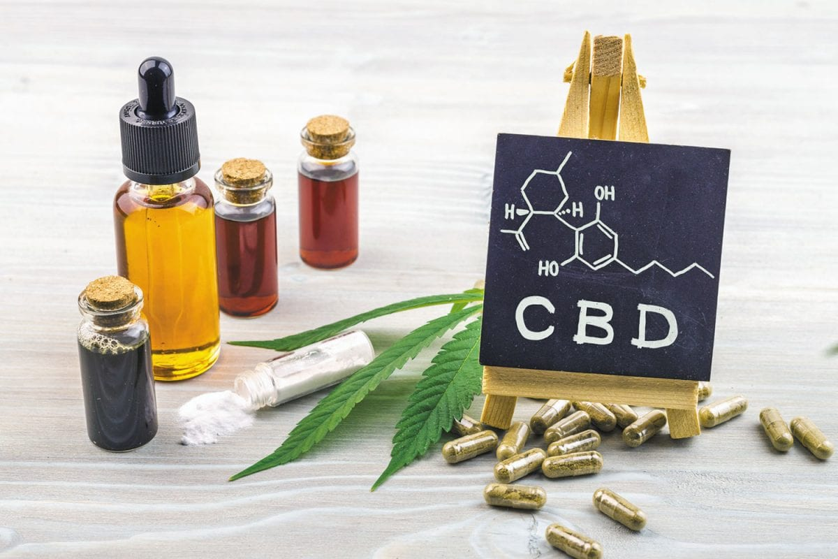 Full spectrum Cannabidiol CBD oils, capsules and crystals isolate with small blackboard with CBD word and chemical structure on wooden backdrop