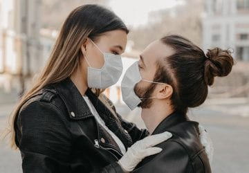a couple wearing face masks holding each other