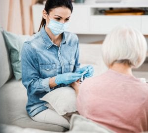 Physician in medical face mask holding syringe while senior lady keeping arm on cushion stock photo